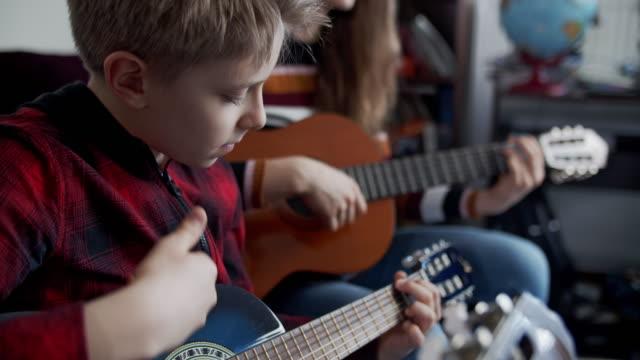 stockvideo's en b-roll-footage met broer en zuster die guitars samen spelen - 10 11 jaar
