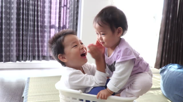 stockvideo's en b-roll-footage met brother and sister playing in the room - wasmand
