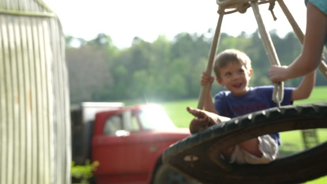 brother and sister playing on a tire swing on the farm super slow motion - einfaches leben stock-videos und b-roll-filmmaterial