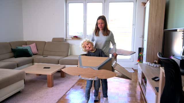 vídeos y material grabado en eventos de stock de hermano y hermana jugando con el avión de cartón en interiores - cartón