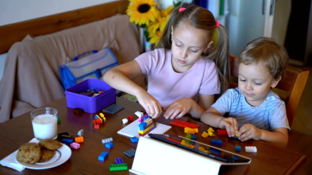 brother and sister playing with colorful bricks at home - skill stock videos & royalty-free footage