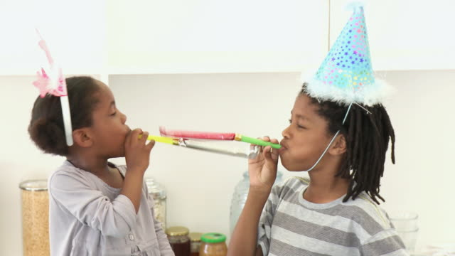 CU Brother (8-9) and sister (4-5) playing with party blowers / Cape Town, Western Cape, South Africa