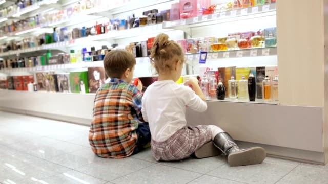 brother and sister playing with perfumes for kids in supermarket, handheld shot - ponytail stock videos & royalty-free footage