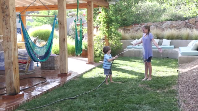 brother and sister playing with water hose - wet stock videos & royalty-free footage