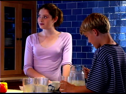 brother and sister preparing food in kitchen - see other clips from this shoot 1335 stock videos and b-roll footage