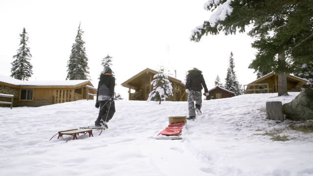 brother and sister pull toboggans back to cabin at winter resort - winter stock videos & royalty-free footage