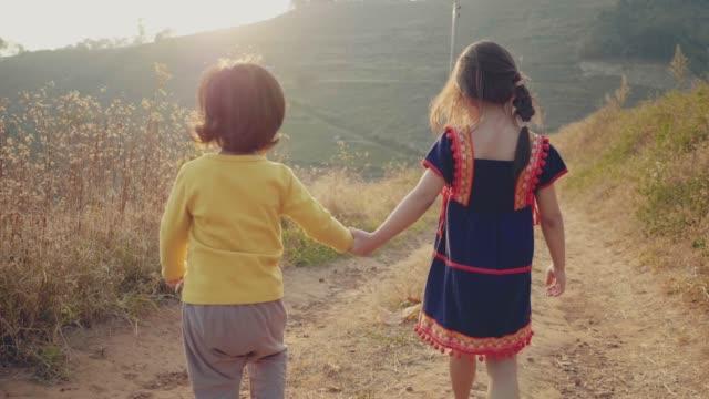 緑豊かな森を走る兄妹 - full length点の映像素材/bロール