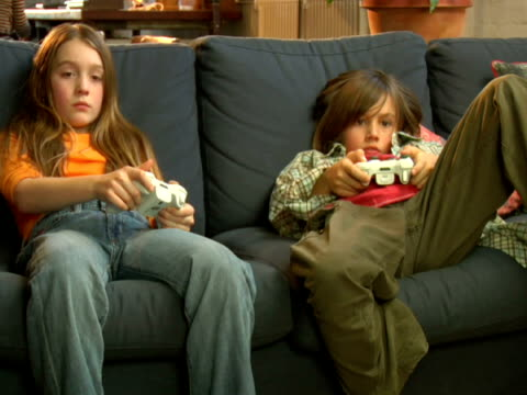 ms, brother (8-9) and sister (10-11) sitting on sofa, playing video game - 10 11 jahre stock-videos und b-roll-filmmaterial