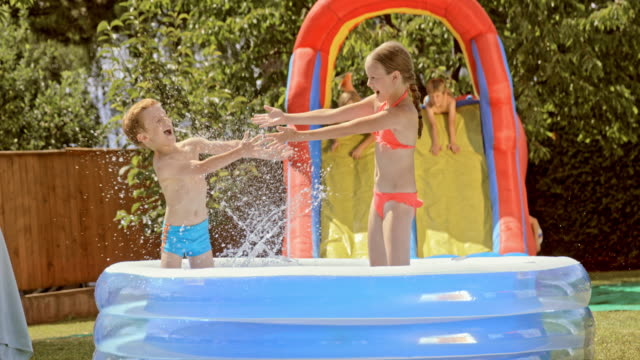 slo mo brother and sister splashing water at each other in an inflatable pool - water slide stock videos & royalty-free footage