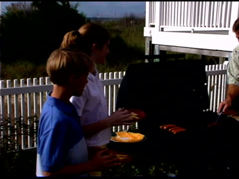 brother and sister standing by parents cooking on patio grill - see other clips from this shoot 1335 stock videos and b-roll footage