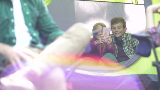 brother and sister taking selfies in tent