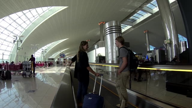 Brother and sister talk on an automatic walkway in an airport