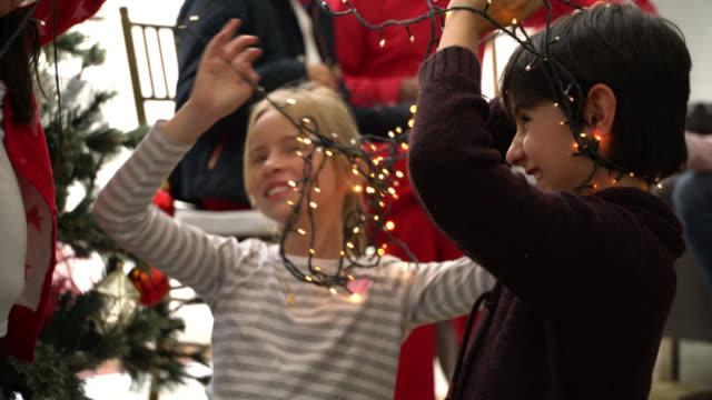 bruder und schwester entwirren die weihnachtsbeleuchtung aus ihrem hals haben spaß bei der dekoration ihres hauses - verziert stock-videos und b-roll-filmmaterial