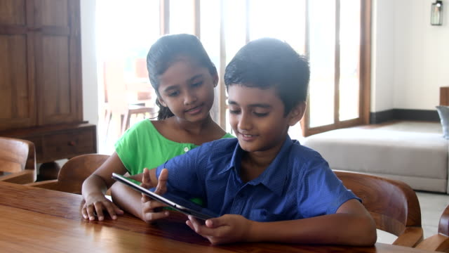 brother and sister using digital tablet at home, smiling - sibling stock videos and b-roll footage