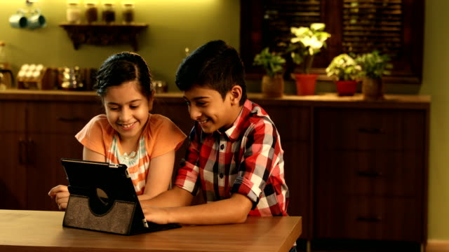 vídeos y material grabado en eventos de stock de ms pan brother and sister using digital tablet in kitchen / delhi, india - nativo digital