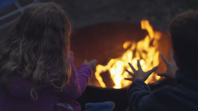 brother and sister warm hands over fire pit on family camping trip to uncompahgre national forest. - camping stock videos & royalty-free footage