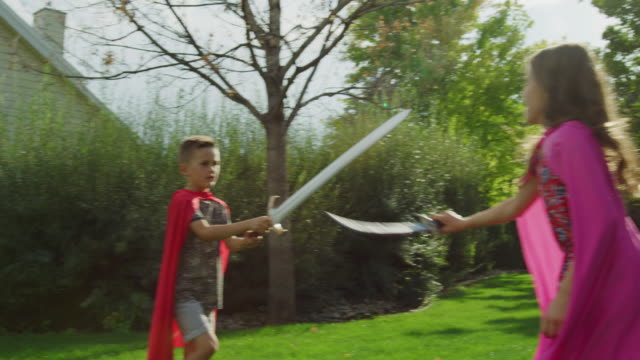 Brother and sister wearing capes fighting with swords on lawn / Pleasant Grove, Utah, United States