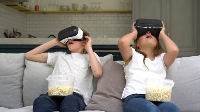 Brother and sister wearing vr glasses and eating pop corn