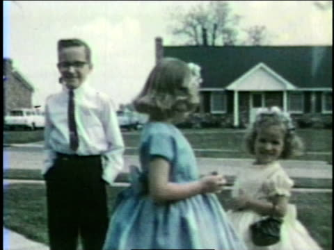stockvideo's en b-roll-footage met a brother and sisters wearing fancy clothes pose in their front yard. - brother
