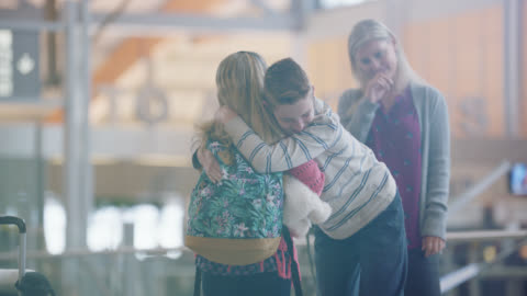 brother hugs young sister good-bye in airport terminal as mother and father look on. - sister stock videos & royalty-free footage
