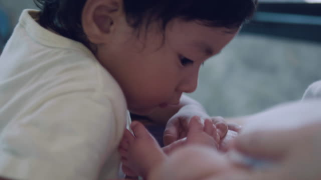 vidéos et rushes de frère embrasser les pieds de son bébé nouveau-né. - frère