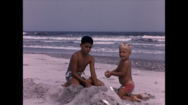 vidéos et rushes de 1955 brother playing with sand at beach - home movie - frère