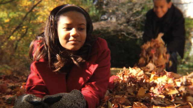 MS Brother (8-9) throwing leaves on sister (12-13) / Montclair, New Jersey, USA