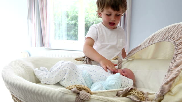 brotherly love - big brother being cute with sleeping baby brother - fratello video stock e b–roll