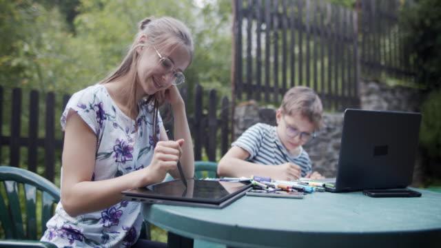vídeos de stock e filmes b-roll de brothers and sister having fun drawing in back yard - terreno