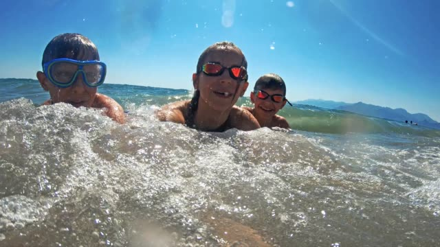 brothers and sister having fun splashed in sea - candid stock videos & royalty-free footage