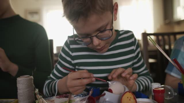 vídeos de stock e filmes b-roll de brothers and sister painting easter eggs - domingo de páscoa