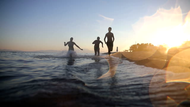Brothers and sister running on beach on sunset.tripping