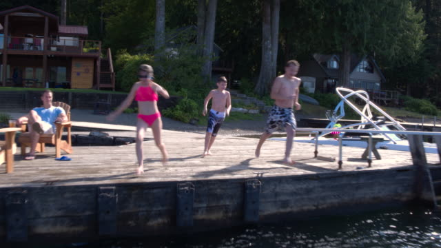 Brothers and sisters jumping into water from jetty, Lake Connaught, Washington, USA.