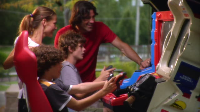 Brothers playing arcade game at amusement park as parents watch over their shoulders and cheer them on