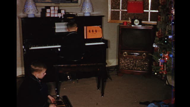 1954 home movie brothers playing piano at christmas time / toronto, canada - 1954 stock-videos und b-roll-filmmaterial