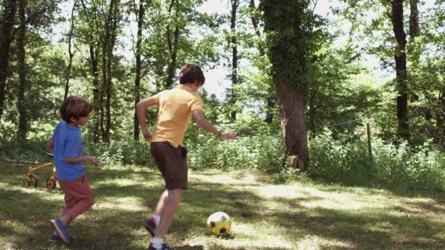 vidéos et rushes de frères de jouer au soccer dans la forêt pendant l'été - balle ou ballon