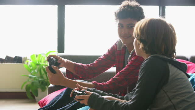 ms brothers playing video games together at home. - boys stock videos & royalty-free footage