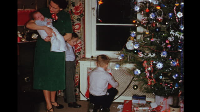 1954 HOME MOVIE Brothers playing with baby sister in mother's arms at Christmas / Toronto, Canada