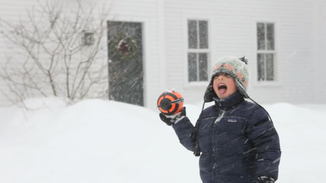 MS PAN Brothers playing with rugby ball during snowstorm  / Yarmouth, Maine, USA