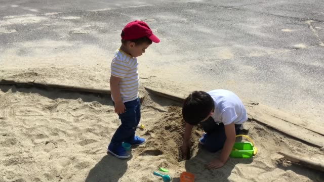 vidéos et rushes de brothers (7 years old and 2 years old) playing with sand - 2 kid in a sandbox