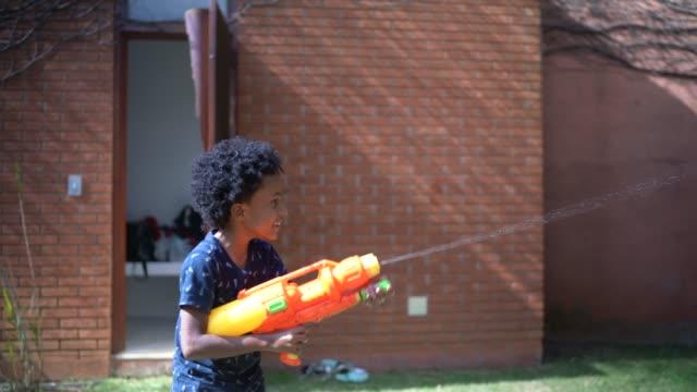 brüder spielen mit spritzpistole in hinterhof - battle stock-videos und b-roll-filmmaterial