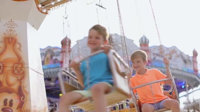 brothers riding on the swings at the fairground - fairground stock videos and b-roll footage