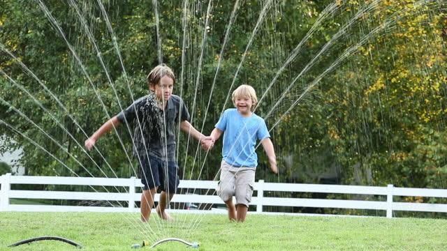 Brothers running through water sprinkler