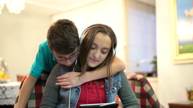 vídeos de stock, filmes e b-roll de usando o tablet em casa de irmãos - aconchegante