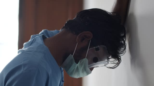 brown asian doctor healthcare worker wearing a surgical mask for protection against  covid-19 coronavirus - india stock videos & royalty-free footage
