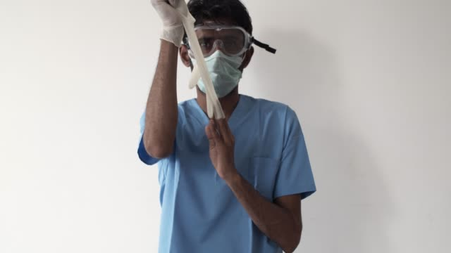 brown asian doctor healthcare worker wearing a surgical mask for protection against  covid-19 coronavirus - rubber glove stock videos & royalty-free footage
