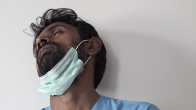 brown asian doctor healthcare worker wearing a surgical mask for protection against  covid-19 coronavirus - exhaustion stock videos & royalty-free footage