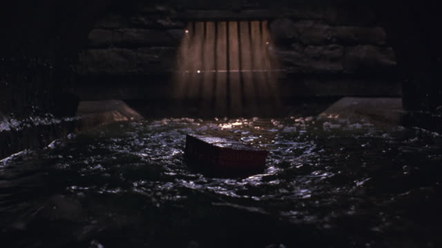 A brown box floats in an underground stream and disappears.