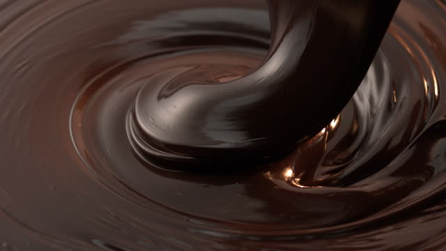 Brown chocolate pouring down in slow motion tabletop