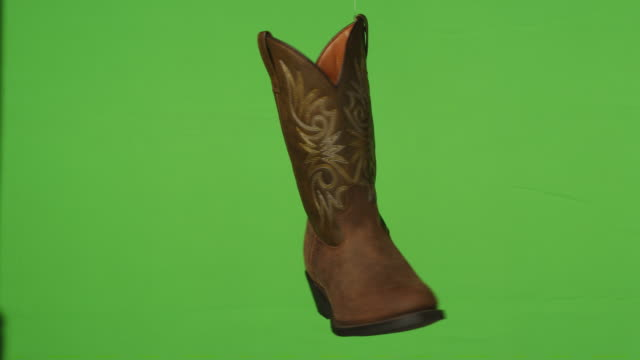 a brown cowboy boot rotates in front of a green screen background. - ranch stock videos & royalty-free footage